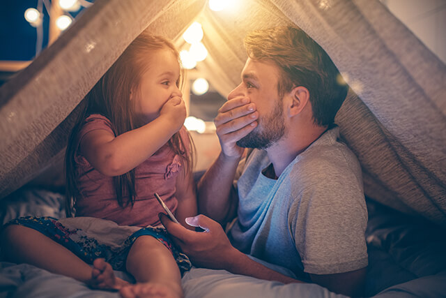 Photo of dad and young daughter in a blanket fort playing.