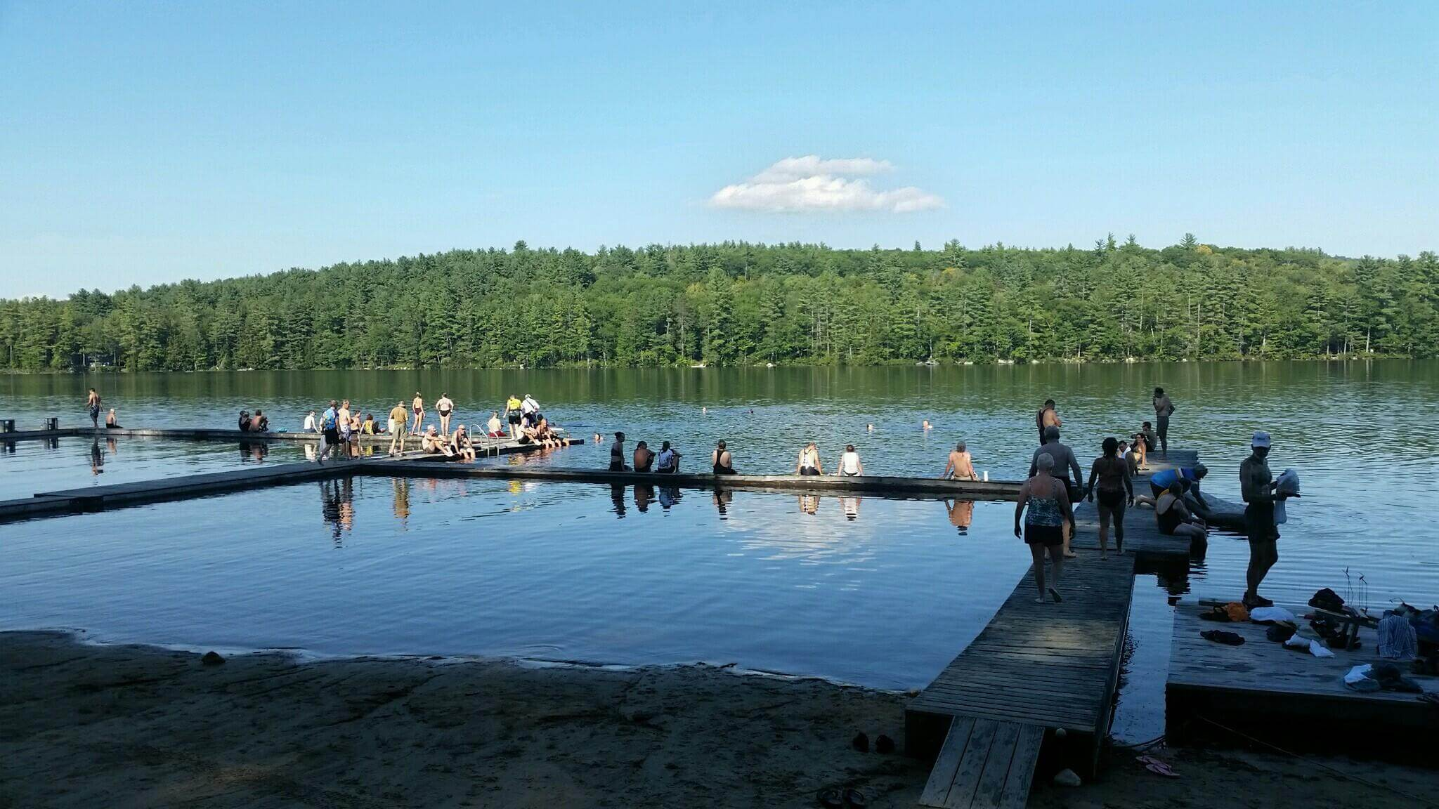 Bike Maine members sitting on a dock and swimming