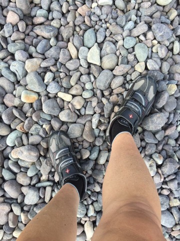 Feet in bike shoes on a rocky surface