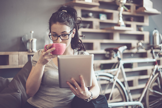Woman sipping her coffee and reading on Tablet