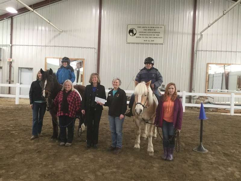 Group of people and horses at a check presentation.