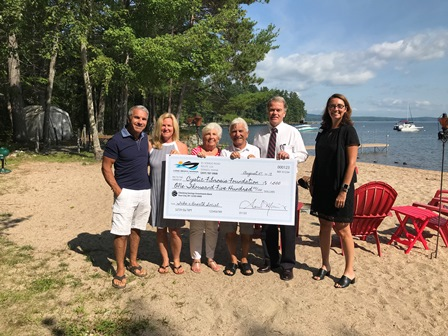 Group of people presenting check on beach