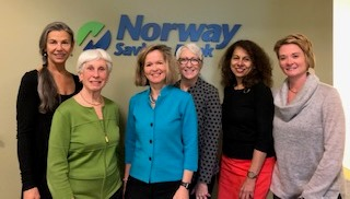 Group of women in front of Norway Savings Bank logo
