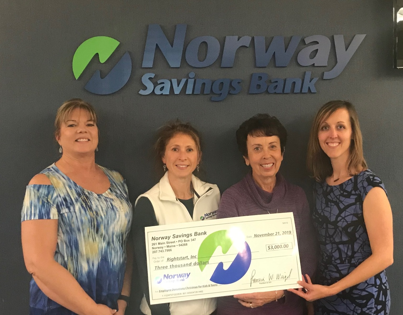 Four women presenting a large check