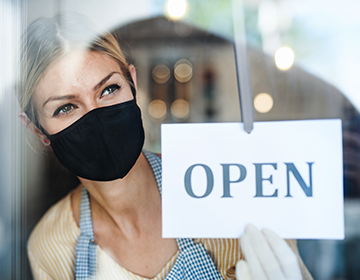 Woman standing in shop window wearing a mask with an open sign